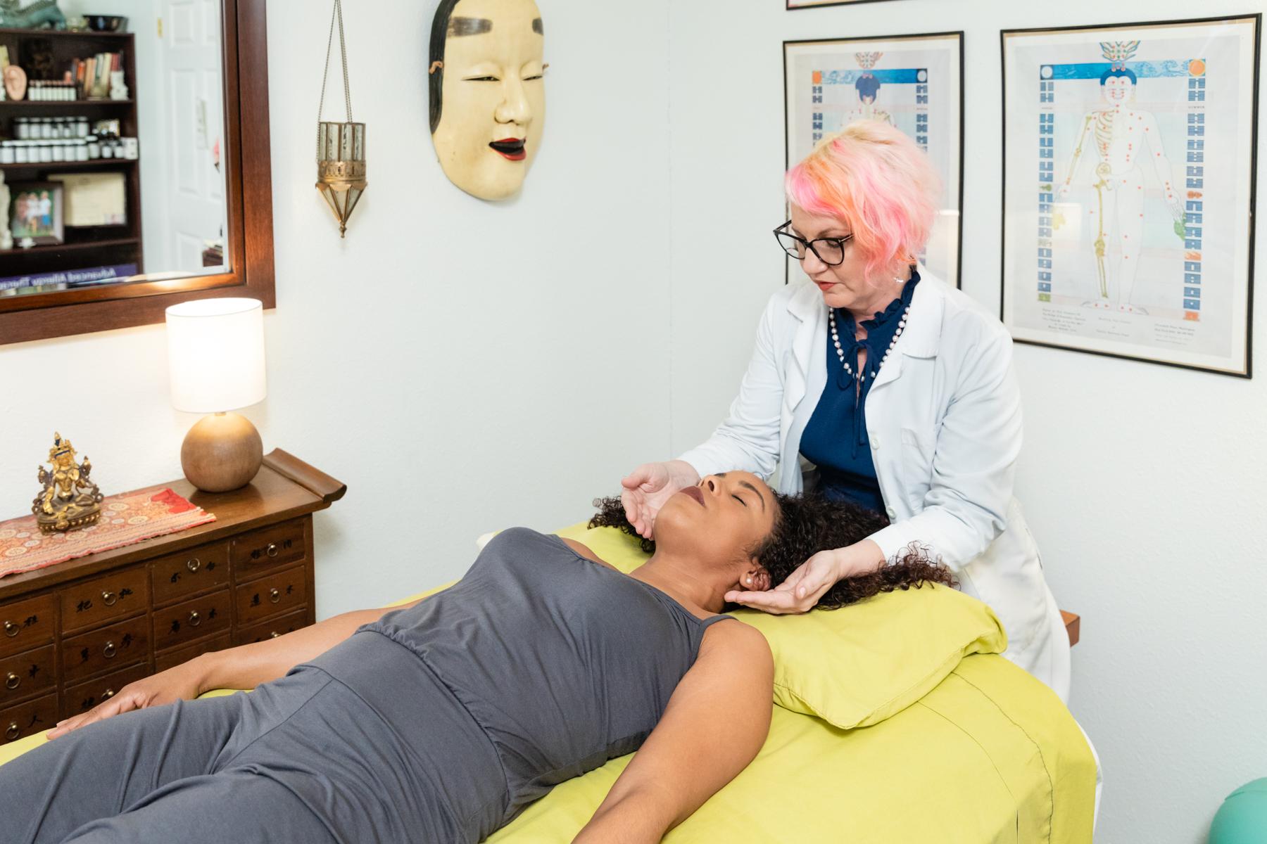 Kymberlie Landgraf Lac works on an acupuncture patient