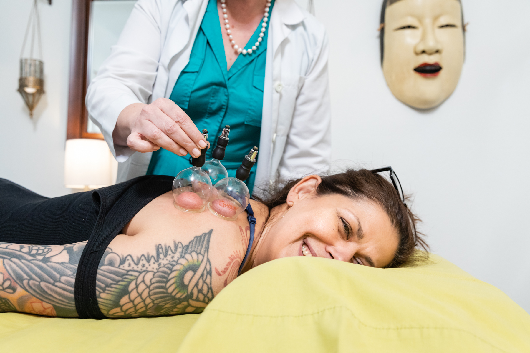 Kymberlie Landgraf Lac applying cupping to patient